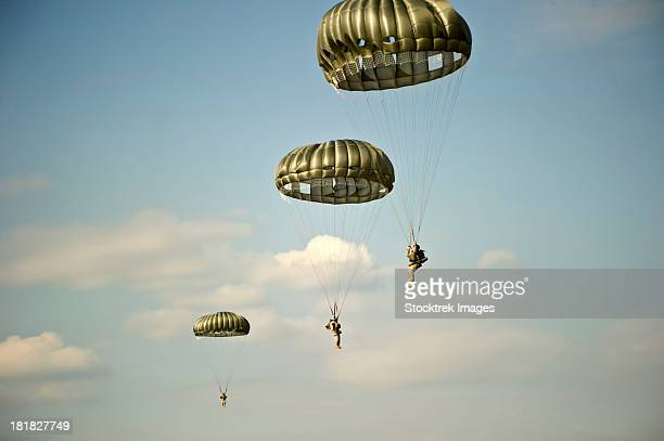january 24, 2013 - u.s. soldiers descend through the sky after exiting a c-23 sherpa aircraft at eglin air force base, florida.  - paratrooper stock pictures, royalty-free photos & images