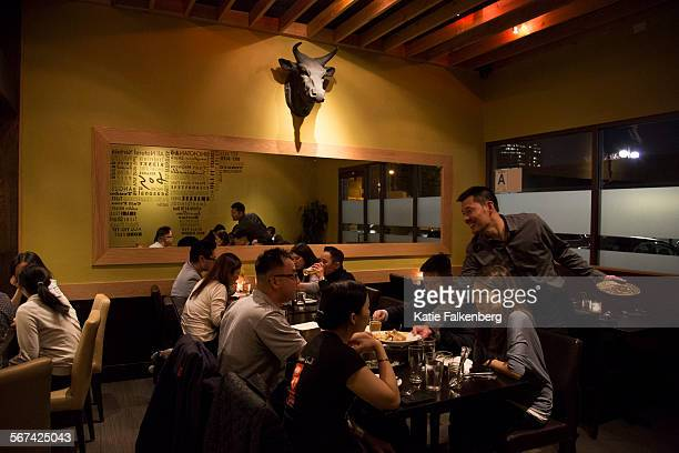 January 25 2014 Jun Isogai right owner of BOS a new restaurant in specializing in nosetotail cooking clears a table of diners at his new restaurant...