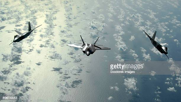 January 28, 2009 - A three-ship formation of F-22 Raptors flies over the Pacific Ocean.