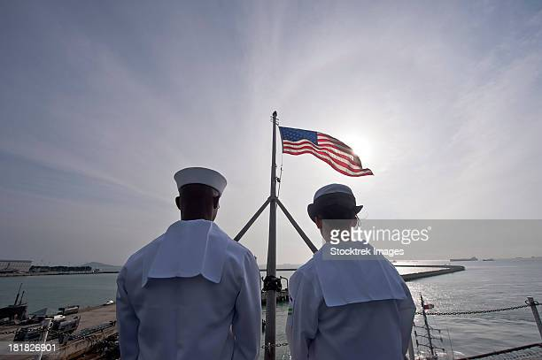 january 30, 2012 - sailors stand by to lower the ensign as the nimitz-class aircraft carrier uss john c. stennis departs singapore.  - us military emblems stock pictures, royalty-free photos & images
