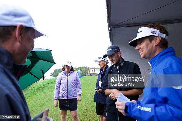 Troy Merritt and his group try to stay dry before they tee off during the ProAm of the Hyundai Tournament of Champions at Kapalua Plantation Course...