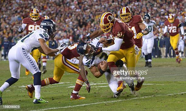 Seattle Seahawks quarterback Russell Wilson is hit by Washington Redskins free safety Madieu Williams and Washington Redskins cornerback DeAngelo...