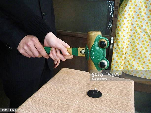 TOKYO Japan A former bride and groom hold a wooden hammer together to smash a wedding ring during a ''divorce ceremony'' in Tokyo's Asakusa district...