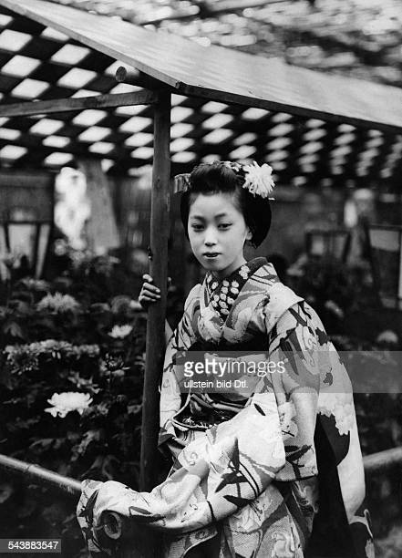 Japan: a maiko in front of flower garden - 1916Vintage property of ullstein bild