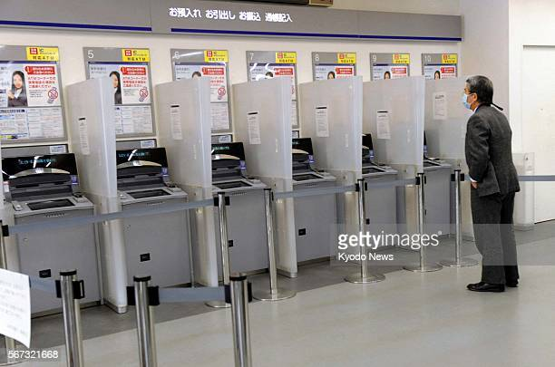 TOKYO Japan A man stands in front of automated teller machines at a Mizuho Bank outlet in Tokyo on March 17 2011 The bank's computer system...