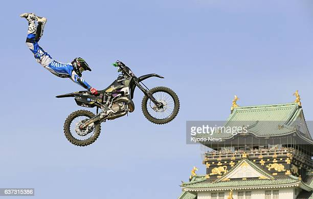 OSAKA Japan A motocross rider performs against the backdrop of the Osaka Castle tower during the Red Bull XFighters World Tour in Osaka Japan on May...