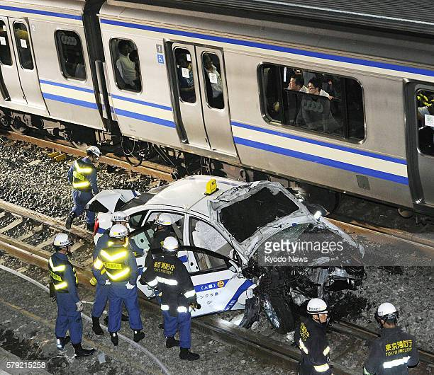 TOKYO Japan A taxi lies on a railway track of East Japan Railway Co after falling from a road and being clipped by an oncoming train in Tokyo's...