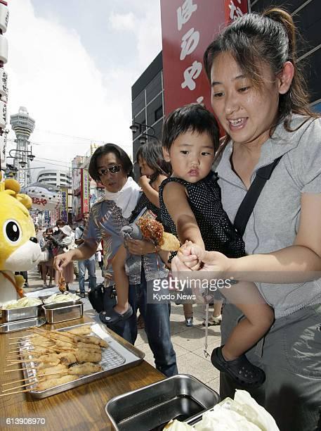 OSAKA Japan A woman and her child pick up 'kushikatsu' skewered pork cutlets in the Shinsekai district in Osaka's Naniwa Ward on Sept 4 2012 One...