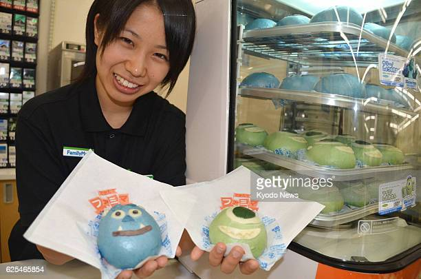 TOKYO Japan A woman holds dumplings featuring characters from the Pixer animation film 'Monsters University' at a FamilyMart Co store in Tokyo's...