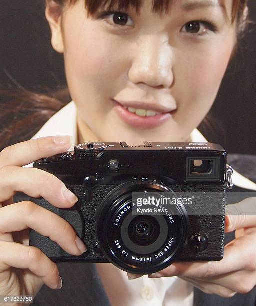 TOKYO Japan A woman holds Fujifilm Corp's XPro1 the company's first digital mirrorless interchangeable lens camera in Tokyo on Jan 26 2012 Fujifilm...