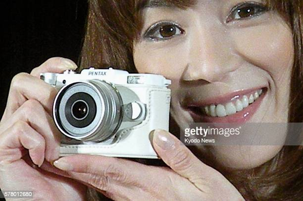 TOKYO Japan A woman holds the pocketsized PENTAX Q in Tokyo on June 23 2011 Japanese optical product maker Hoya Corp said it will soon launch the...