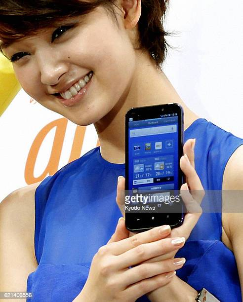 TOKYO Japan Actress Ayame Goriki holds a new smartphone to be sold by KDDI Corp during a promotional event in Tokyo on May 20 2013 KDDI will begin...