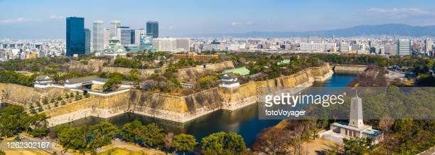 japan aerial panorama osaka castle park overlooked by skyscrapers - moat stock pictures, royalty-free photos & images