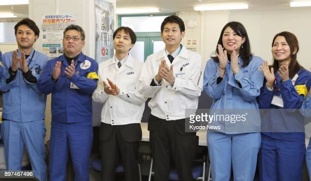 Japan Aerospace Exploration Agency and Mitsubishi Heavy Industries Ltd staff applaud after the launch of the H2A rocket from Tanegashima Space Center...