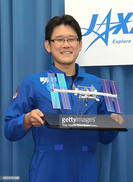 Japan Aerospace Exploration Agency astronaut Norishige Kanai poses for photographs during a press conference at the JAXA Tokyo office on August 27...