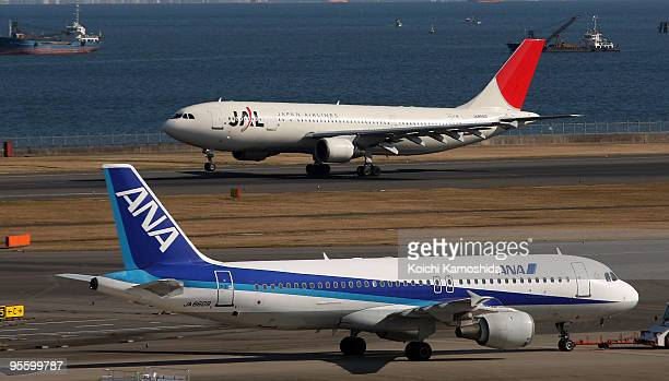 Japan Airlines and All Nippon Airways passenger planes sit on the tarmac of Tokyo International Airport on January 6 2010 in Tokyo Japan Asia's...