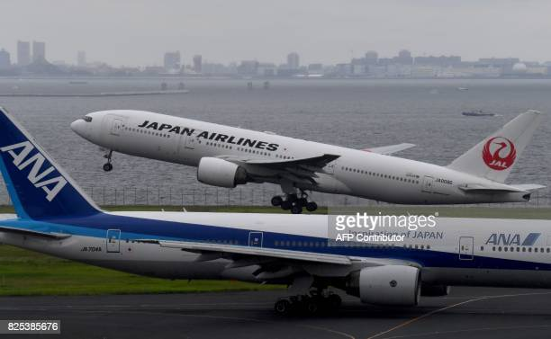 A Japan Airlines Boeing 777 jetliner takes off beside All Nippon Airways jetliner at Haneda international airport in Tokyo on August 2 2017 / AFP...
