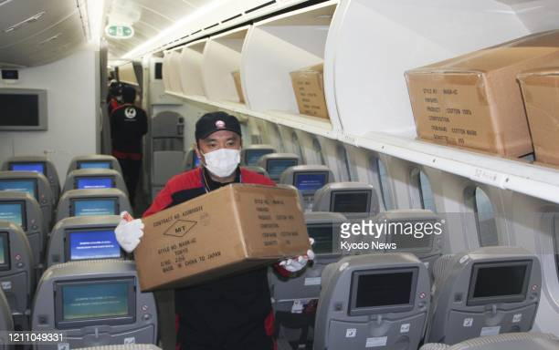 Japan Airlines Co. Employee carries a box of medical masks from the luggage hold of a plane at Narita airport near Tokyo on April 22, 2020. Major...
