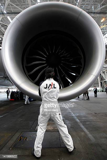 A Japan Airlines Co employee looks at a General Electric Co engine on the Boeing Co 787 Dreamliner aircraft during a media preview at Narita Airport...