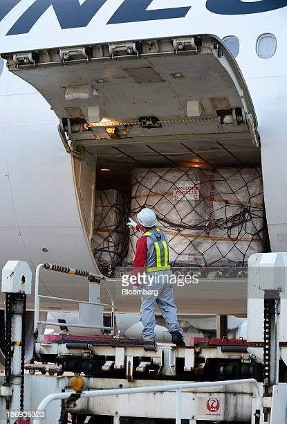 A Japan Airlines Co employee unload a cargo containing boxes of Beaujolais Nouveau wine from the storage space of an aircraft at Haneda Airport in...