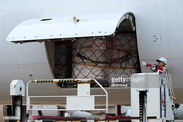 A Japan Airlines Co employee unloads a cargo containing boxes of Beaujolais Nouveau wine from the storage space of an aircraft at Haneda Airport in...