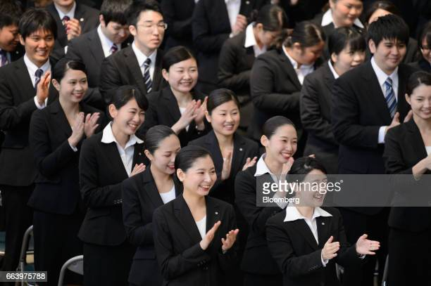 Japan Airlines Co group companies' new employees applaud during an initiation ceremony at one of the company's hangers near Haneda Airport in Tokyo...