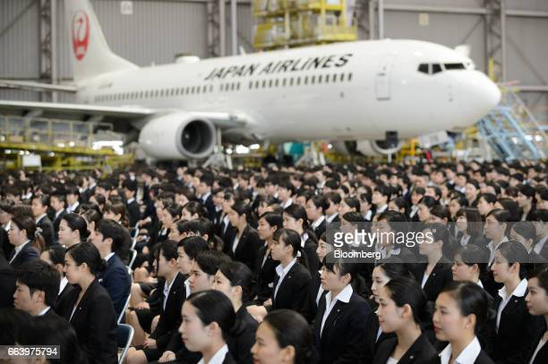 Japan Airlines Co group companies' new employees attend an initiation ceremony at one of the company's hangers near Haneda Airport in Tokyo Japan on...
