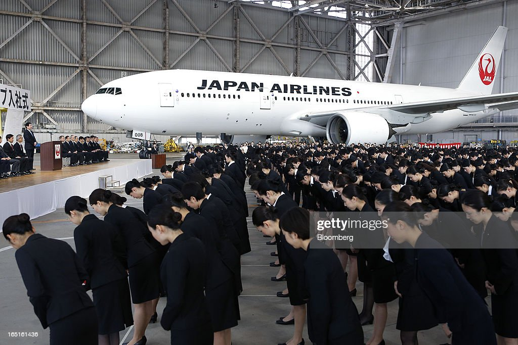 Japan Airlines Co. (JAL) group companies' new employees bow following an address by Yoshiharu Ueki, president of Japan Airlines Co. (JAL), standing on a stage, during a welcoming ceremony at the company's hangar near Haneda Airport in Tokyo, Japan, on Monday, April 1, 2013. Japan's jobless rate dropped to 4.2 percent in January from 4.3 percent in December in an indication that newly elected Prime Minister Shinzo Abe's drive to boost the economy with anti-deflation policies may be paying off. Photographer: Kiyoshi Ota/Bloomberg via Getty Images
