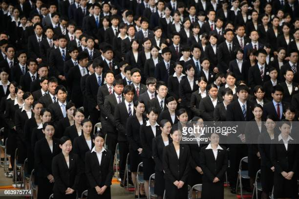 Japan Airlines Co group companies' new employees pose for photographs during an initiation ceremony at one of the company's hangers near Haneda...