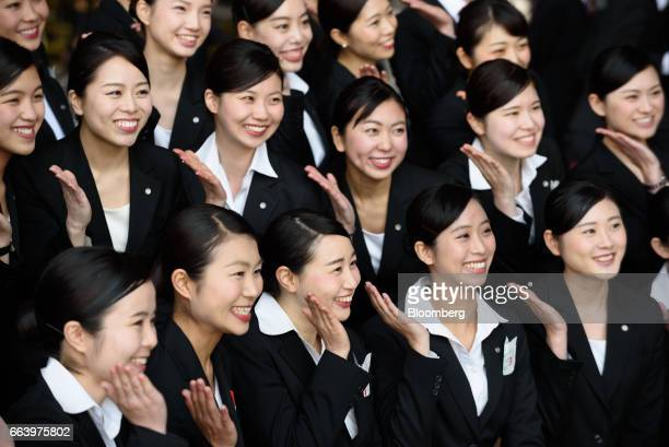 Japan Airlines Co group companies' new employees pose for photographs after an initiation ceremony at one of the company's hangers near Haneda...