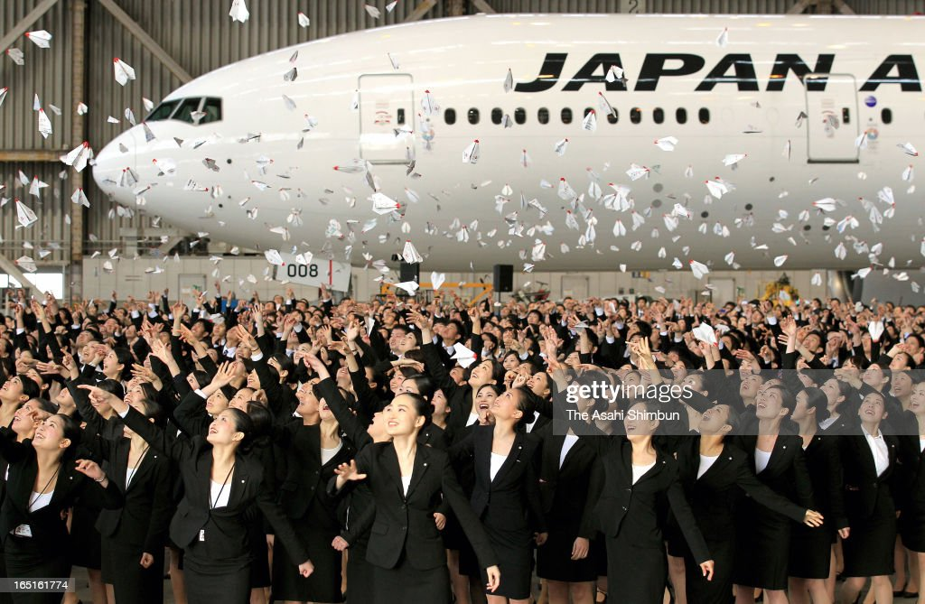 Japan Airlines Co (JAL) new emplyees release paper planes during their welcome ceremony held at their hanger at Haneda Airport on April 1, 2013 in Tokyo, Japan. New recruits, most of them are newly graduates from colleges, make the first step at work at the start of the Japan's fiscal year 2013.