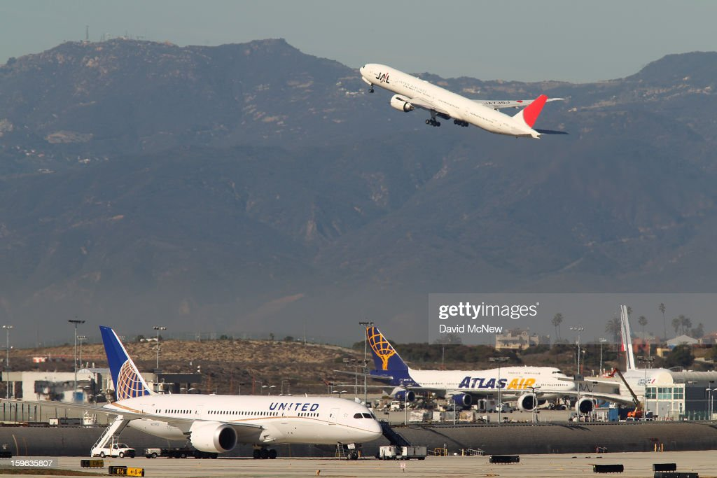 A Japan Airlines (JAL) jet takes off behind a grounded Boeing 787 Dreamliner jet (L) operated by United Airlines parked at Los Angeles International Airport (LAX) on January 17, 2013 in Los Angeles, California. The Federal Aviation Administration has grounded all U.S.-registered Boeing 787 Dreamliner jets for the repair of batteries believed to be linked to a fire risk following a number of related 787 aircraft incidents this month.