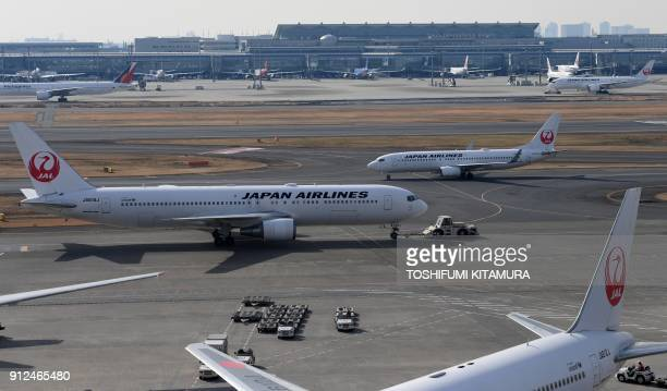 Japan Airlines passenger jets taxi at Haneda International Airport in Tokyo on January 31 2018 Japan Airlines on January 31 reported a rise in net...