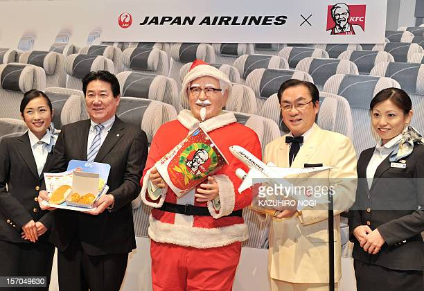 Japan Airlines President Yoshiharu Ueki and Masao Watanabe President of Kentucky Fried Chicken Japan pose with a statue of Colonel Sanders wearing a...