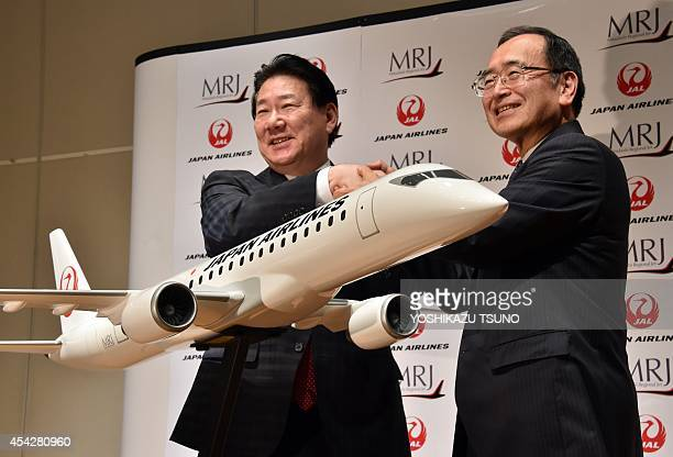 Japan Airlines president Yoshiharu Ueki shakes hands with Japan's Mitsubishi Aircraft chairman Hideo Egawa as they announce that JAL ordered...