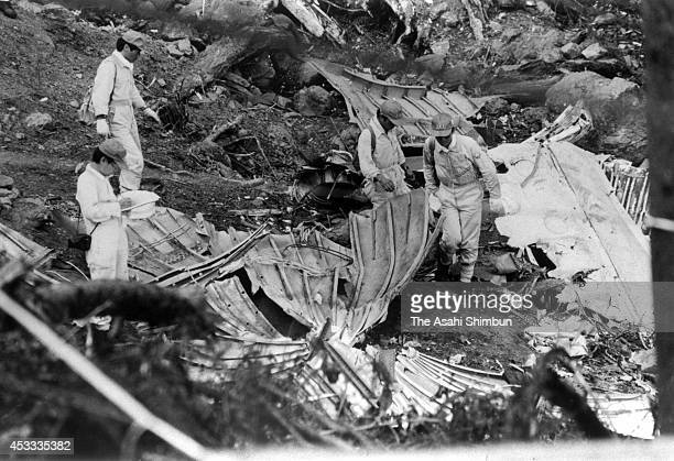 Japan Airlines staffs investigate the debris of the aft pressure bulkhead at the crash site at the ridge of Mount Osutaka on August 18, 1985 in Ueno,...