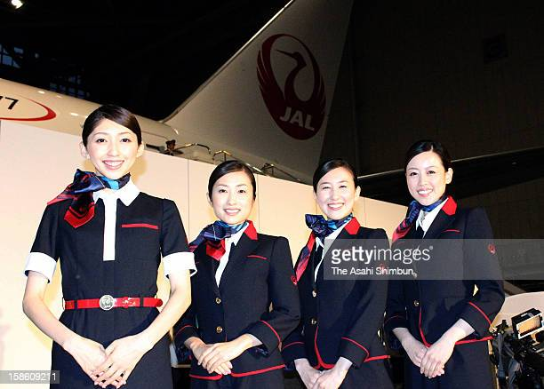 Japan Airlines staffs poses for photographs with their new uniforms designed by Keita Maruyama at the press preview at Tokyo International Airport on...