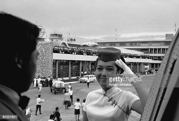 A Japan Airlines stewardess welcomes The Beatles to Kaitak Airport Hong Kong where the group will board a connecting flight to Manila on their final...