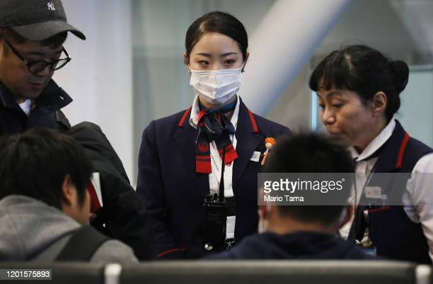 Japan Airlines worker wears a face mask while working inside a terminal at Los Angeles International Airport on January 23 2020 in Los Angeles...