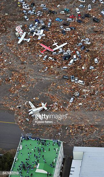 SENDAI Japan Airplanes and cars are covered with debris at Sendai airport in Miyagi Prefecture northeastern Japan on March 11 after a tsunami...