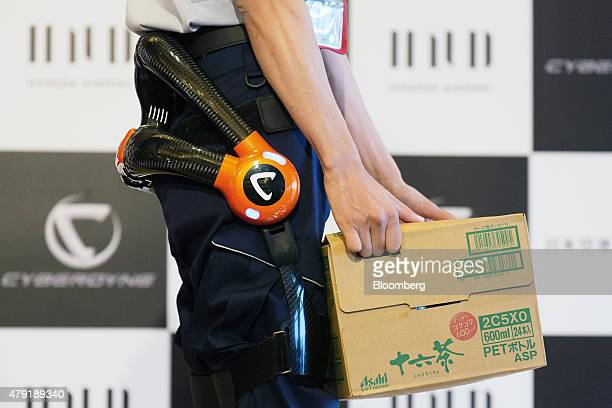 A Japan Airport Terminal Inc employee carries a box while wearing the Hybrid Assistive Limb exoskeleton robot suit developed by Cyberdyne Inc during...