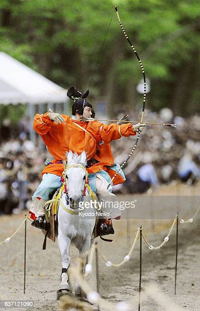 KYOTO Japan An archer in traditional costume shoots an arrow while riding a horse at full speed during the annual Yabusame Shinji event at Shimogamo...