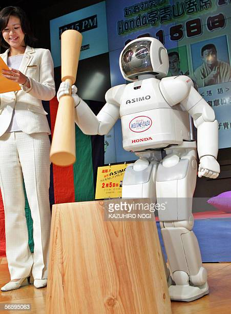 An employee of Japan's auto giant Honda Motor introduces its humanoid robot Asimo making a rice cake at Honda's Tokyo headquarters 15 January 2006 as...