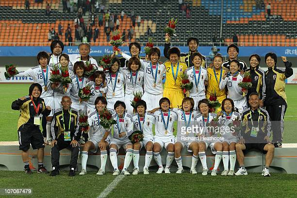 Japan celebrates on the medal stand after defeating North Korea 10 to win the gold medal after the women's gold medal football match at Tianhe...