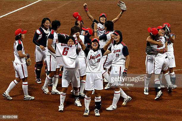 Japan celebrates their 3-1 win against the United States during the women's grand final gold medal softball game at the Fengtai Softball Field during...