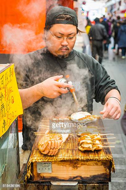 Japan chef cooking seafood street market food stall Osaka Japan