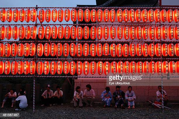 Japan Chiba Narita Festival goers at the Gion Matsuri rest under rows of illuminated chochin lanterns with name of donor to Narita san Temple written...