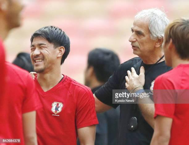 Japan coach Vahid Halilhodzic talks to Shinji Okazaki before a training session in Jeddah Saudi Arabia on Sept 4 a day before the last match in the...