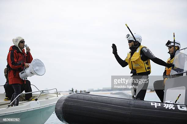 Japan coast guards listen to a protestor as people use motor boats and kayaks to defy Japan Coast Guard in the Oura Bay to protest against the...