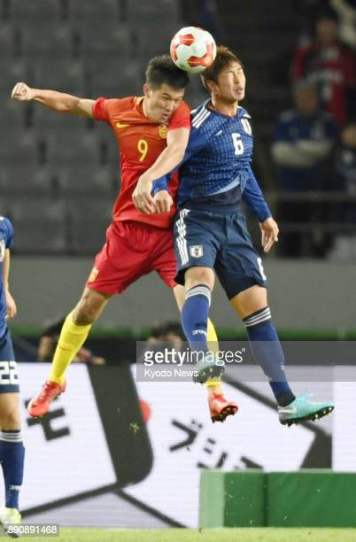 Japan defender Genta Miura and China striker Xiao Zhi vie for the ball in the first half of a men's match of the F1 Football Championship at...